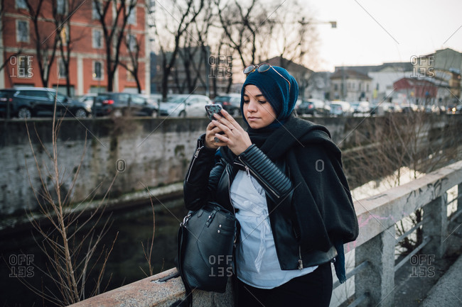 Young woman in hijab looking at smartphone by canal in city
