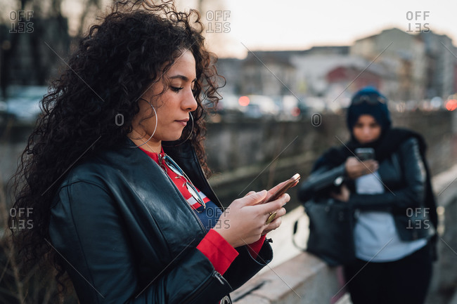 Mid adult woman with long curly hair looking at smartphone by city canal