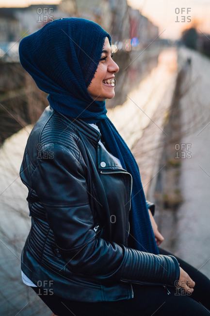 Happy young woman in hijab by city canal