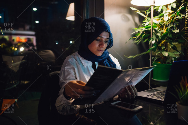 Young woman in hijab looking at menu in cafe
