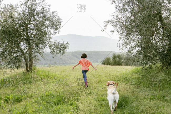 Girl running with labrador dog in scenic field landscape, rear view, Citta della Pieve, Umbria, Italy