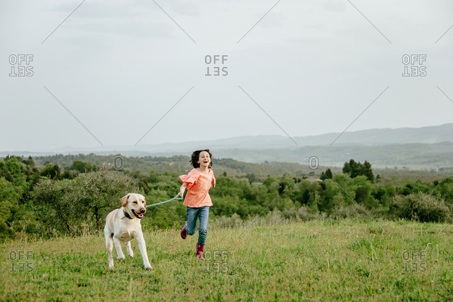 Girl running with labrador dog in scenic field landscape, Citta della Pieve, Umbria, Italy