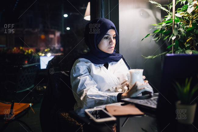 Young woman in hijab looking at laptop in cafe