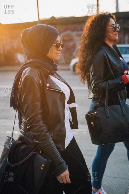 Young woman in hijab and best friend strolling in city