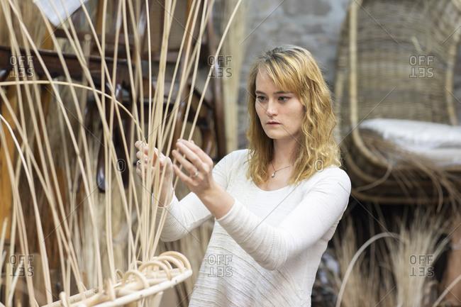 Young female basket maker weaving in workshop