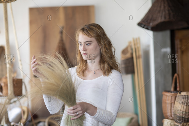 Young female basket maker examining dried grasses in workshop
