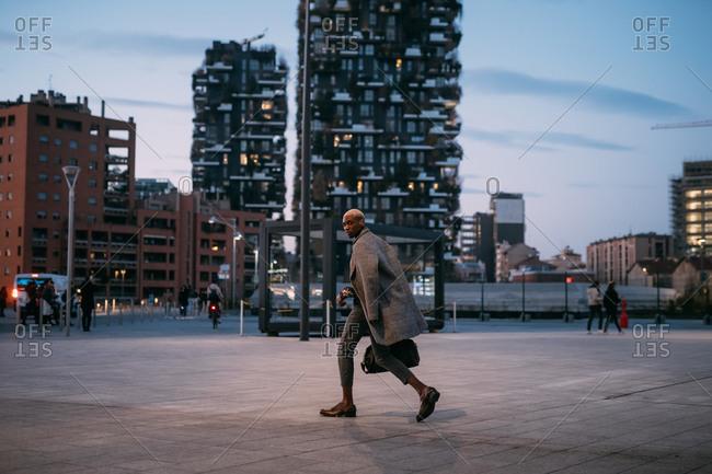 Stylish man walking through piazza, Milan, Italy