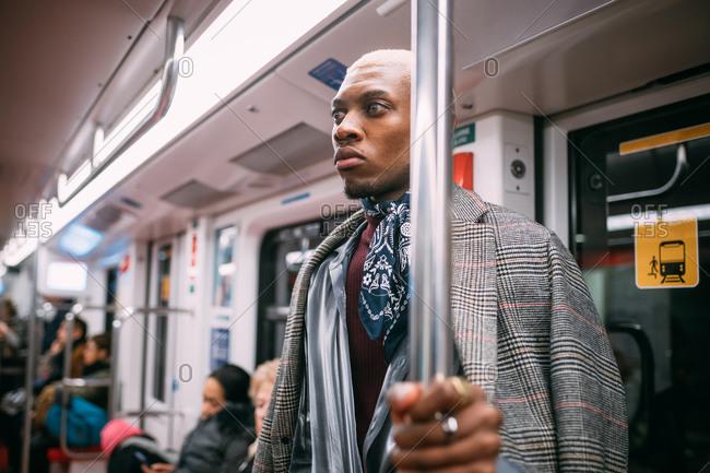Stylish man daydreaming in train, Milan, Italy