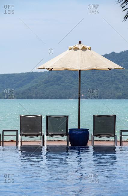 Sun umbrellas and loungers by infinity pool at resort, Rawai, Phuket, Thailand