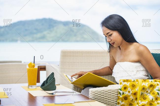 Woman reading menu at seaside resort, Rawai, Phuket, Thailand