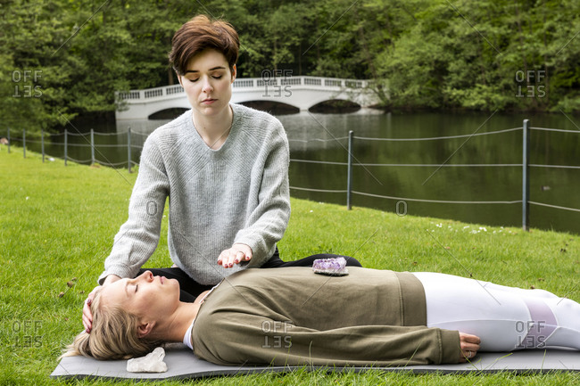 Woman practicing Reiki on grass lawn by river, London, UK