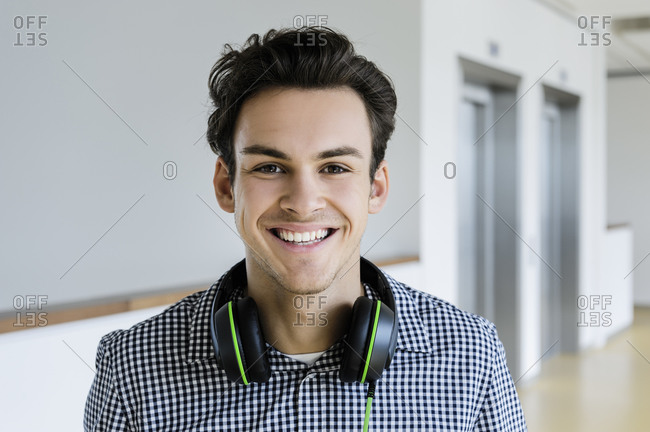 Businessman with headphones in office corridor