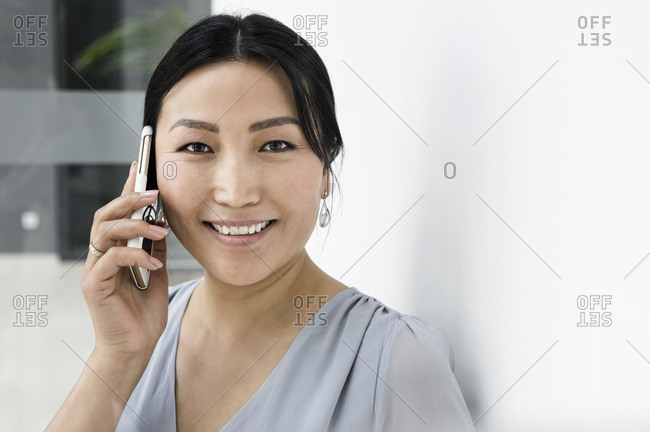 Businesswoman using smartphone against white wall in office