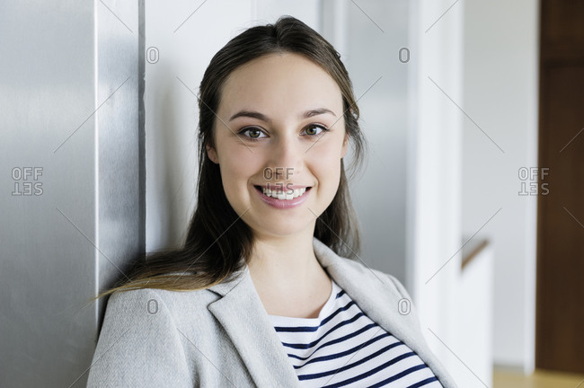 Businesswoman leaning against elevator door