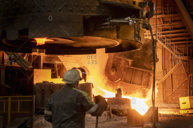 Steelworker looking on as molten steel flask is emptied during steel pour in steelworks