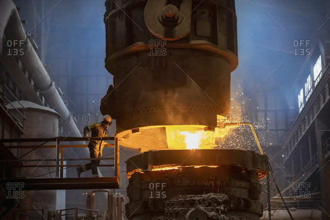 Steelworker inspecting molten steel during steel pour in steelworks