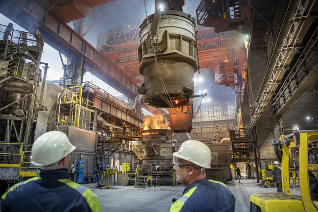 Steelworkers making molten steel pour into vacuum mould in steelworks