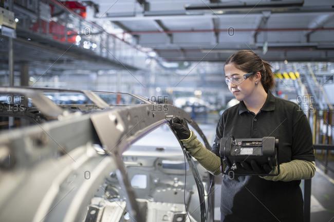 Female engineer testing car body in car factory