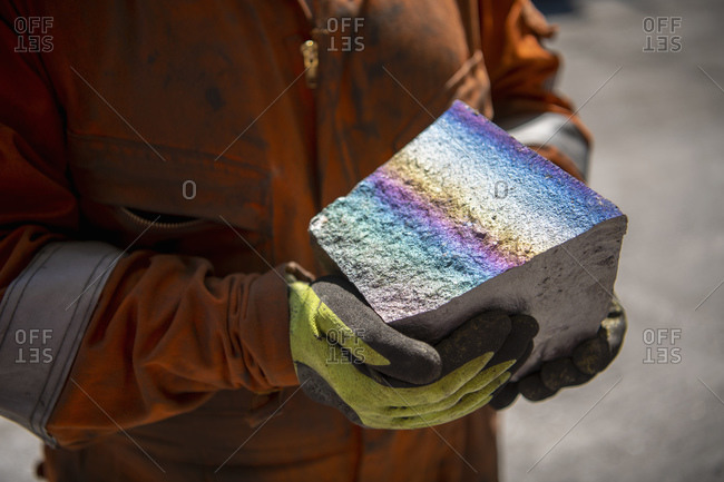 Worker holding fractured block of titanium alloy with colored iridescence in titanium recycling plant