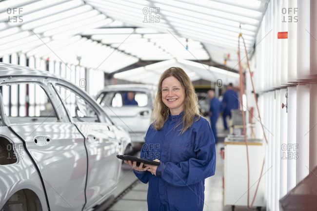 Portrait of female worker with digital tablet in paint inspection area of car factory