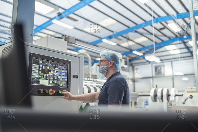 Worker controlling printer in print factory
