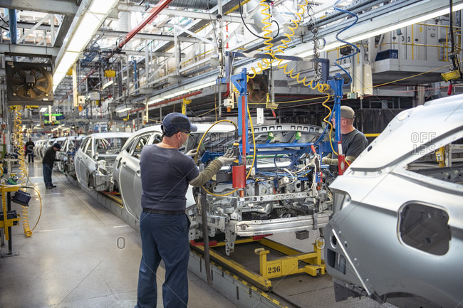 Car workers fitting bonnets to cars on production line in car factory