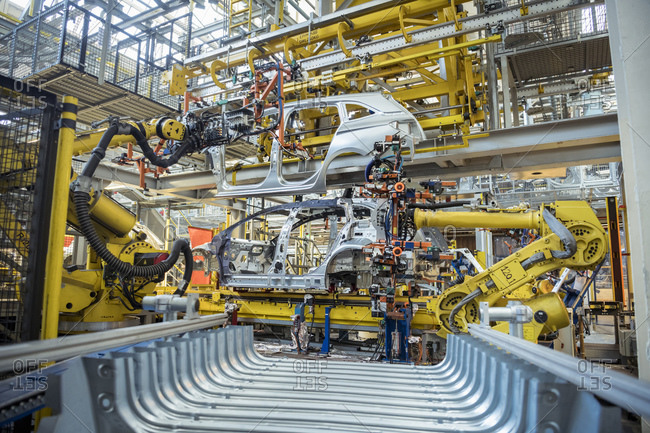 Robots with car body on production line in car factory