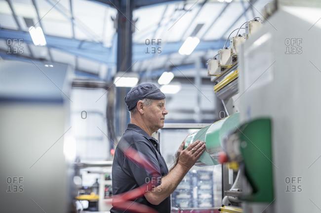 Worker loading plastic packaging in print machine in print factory