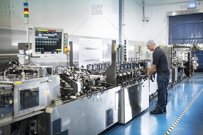Worker with food packaging printing machine in print factory