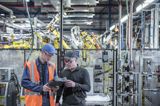Apprentice engineer with mentor programming robots in car factory