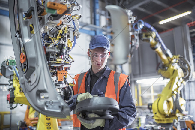 Apprentice engineer programming robots in car factory