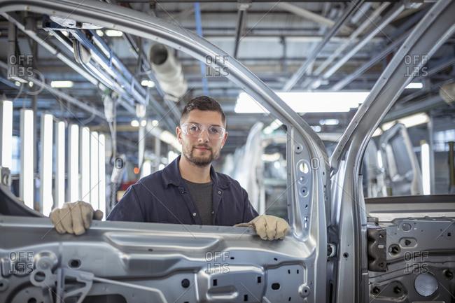 Portrait of car body inspector in car factory