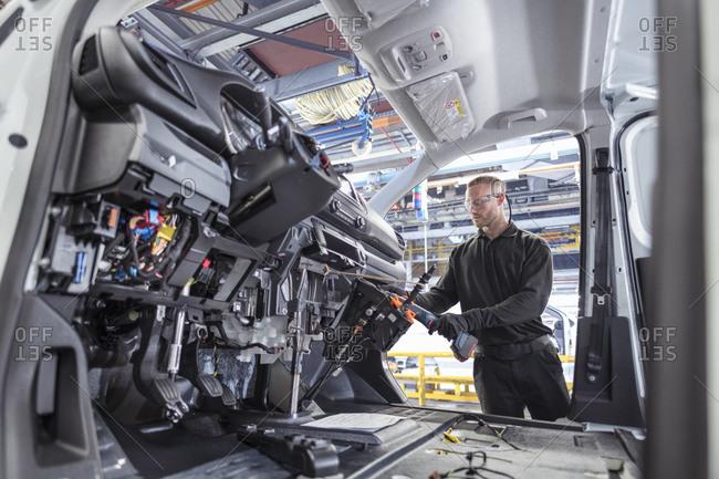 Engineer working on interior of van in car factory