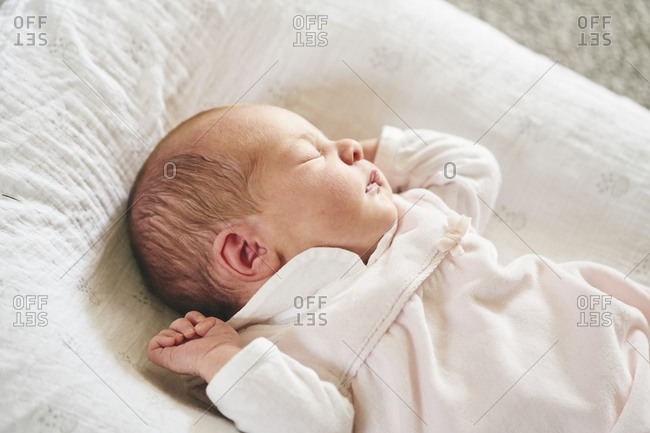 Baby sleeping on U-shaped pillow at home