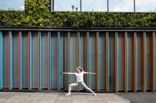 Young woman practicing yoga pose on city sidewalk, arms and legs outstretched