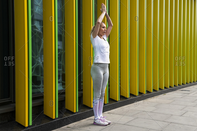 Young woman practicing yoga pose with hands together on city sidewalk, full length