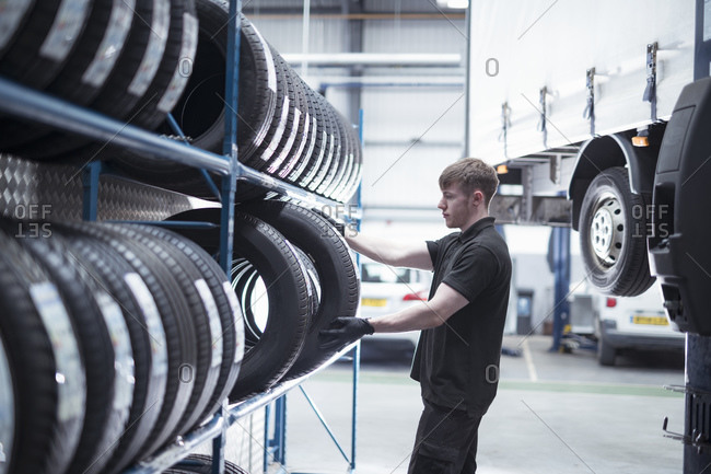 Apprentice engineer selecting tires in car service center