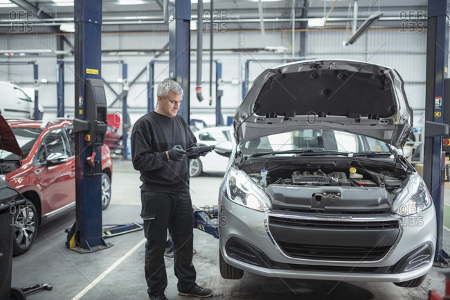 Engineer inspecting car in car service center