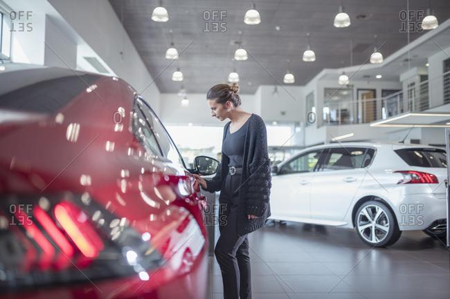Female customer inspecting new car in car showroom