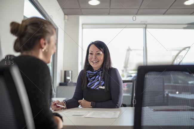 Saleswoman talking to customer in car dealership