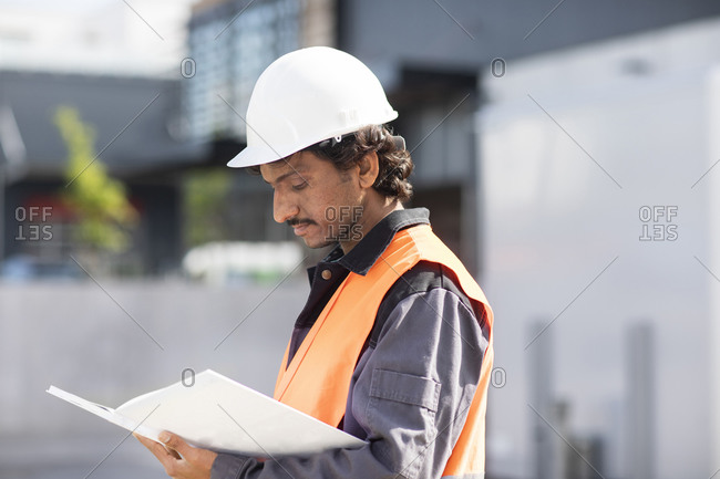 Male engineer looking at plans by industrial building