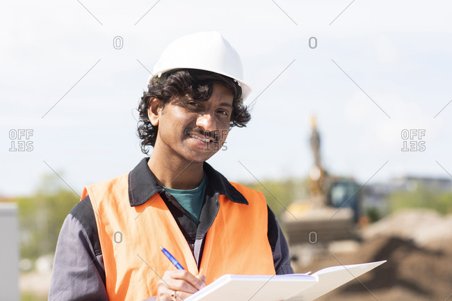 Male engineer on construction site writing in notebook, head and shoulder portrait