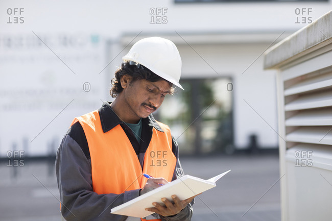 Male engineer outside industrial building writing in notebook