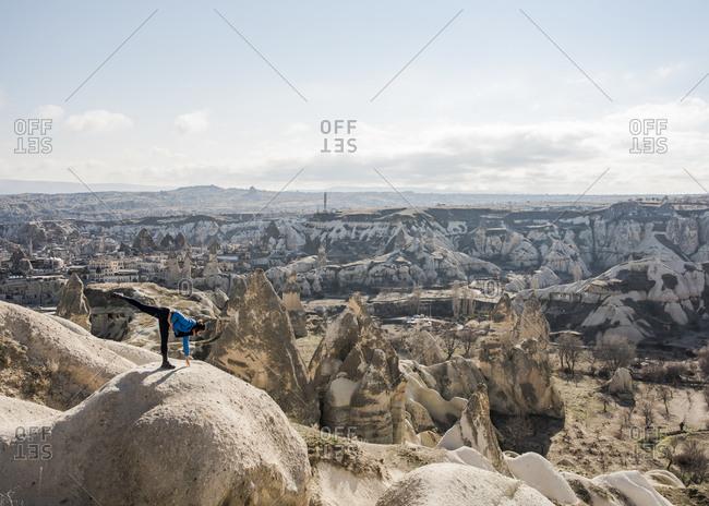 Woman practicing yoga on top of rock, Goreme, Cappadocia, Nevsehir, Turkey