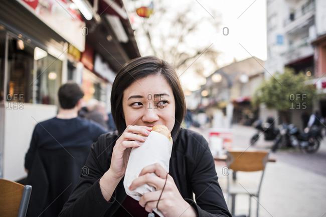 Woman eating kebab bread at cafe, Kusadasi, Izmir, Turkey