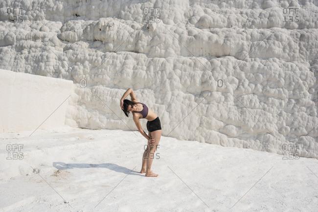 Woman practicing yoga in cotton castle, Pamukkale, Denizli, Turkey