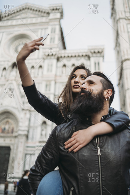 Couple playing piggyback ride and taking selfie, Santa Maria del Fiore, Firenze, Toscana, Italy