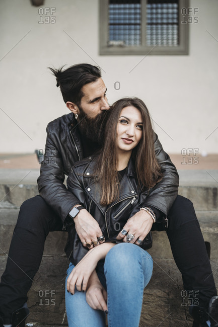 Man kissing hair and hugging woman from behind on steps