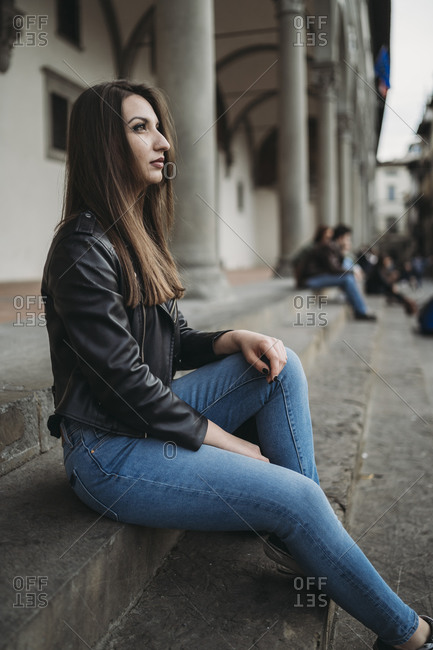 Woman sitting on steps and daydreaming