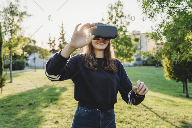 Young woman looking through VR headset in park